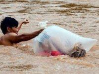 Seorang pria rela seberangi sungai berlumpur dan lindungi anak-anak agar bisa sekolah (Sumber: World of Buzz)