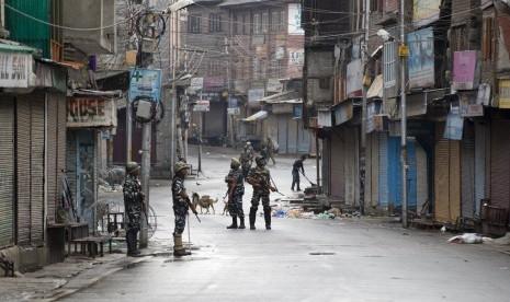 Tentara paramiliter India berjaga di jalanan yang sepi saat jam malam di Srinagar, Kashmir yang dikuasai India