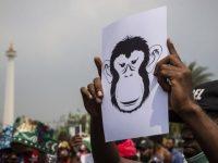 Massa yang tergabung dalam Mahasiswa Papua Anti Rasisme, Kapitalisme, Kolonialisme dan Militerisme membentangkan poster saat menggelar unjuk rasa di seberang Istana Merdeka