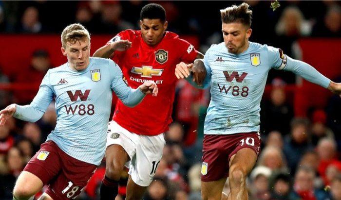 Matt Targett (kiri) mengawal Marcus Rashford pada pertandingan Manchester United vs Aston Villa. (c) AP Photo