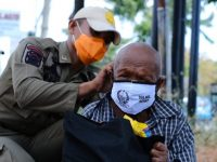 Saat petugas memakaikan masker untuk Warga di Makassar.
